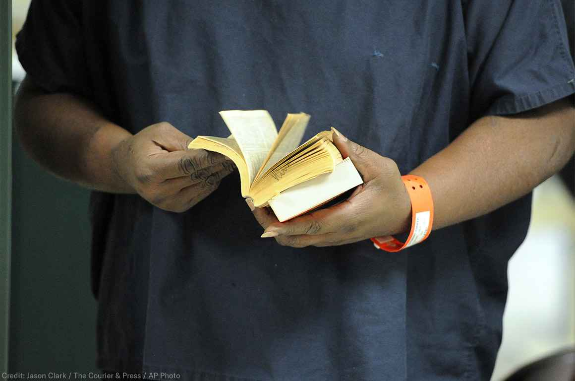 An incarcerated person thumbs through a book