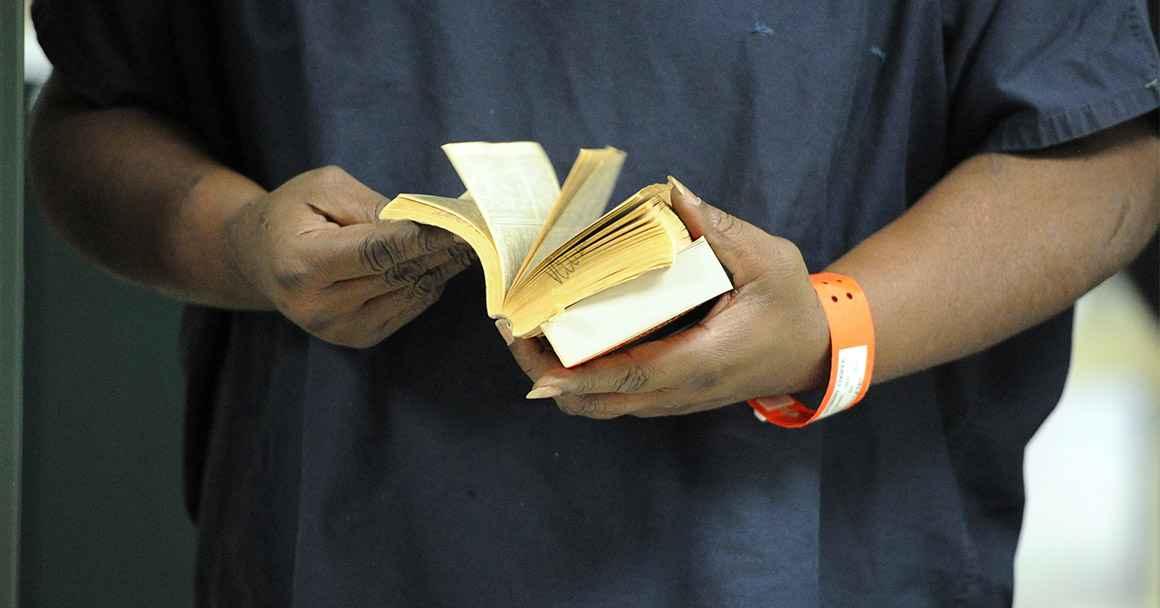 An incarcerated person thumbs through a book